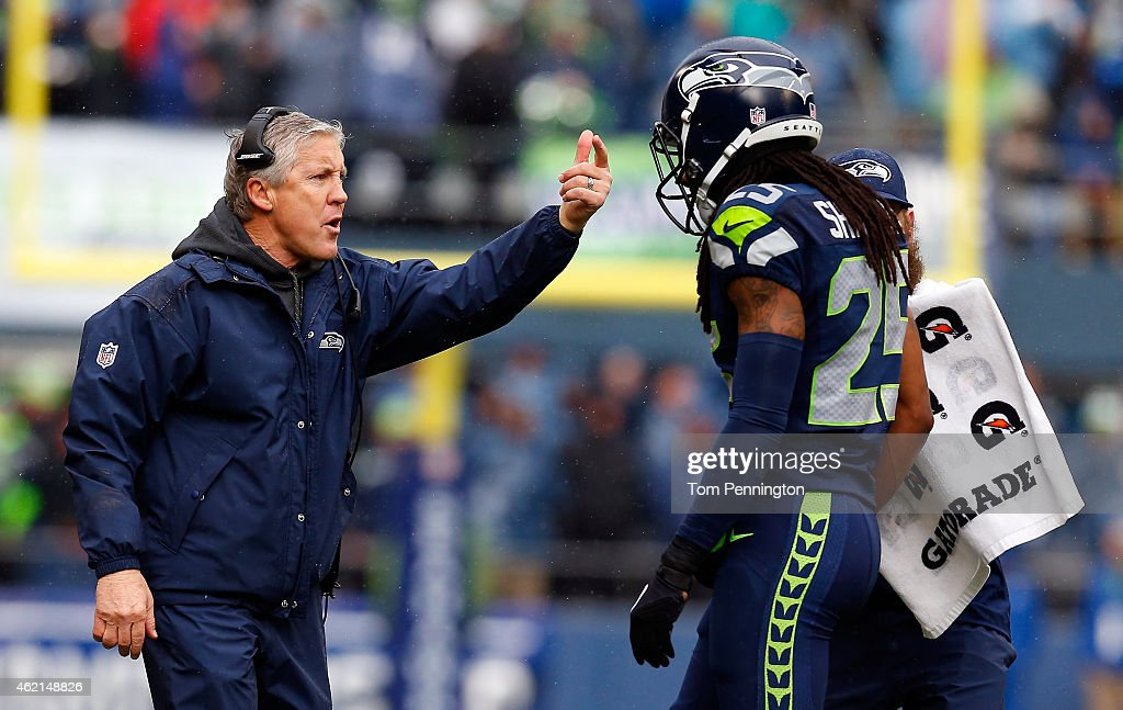 Richard Sherman #25 speaks with head coach Pete Carroll of the Seattle Seahawks against the Green Bay Packers during the 2015 NFC Championship game at CenturyLink Field on January 18, 2015 in Seattle, Washington.
