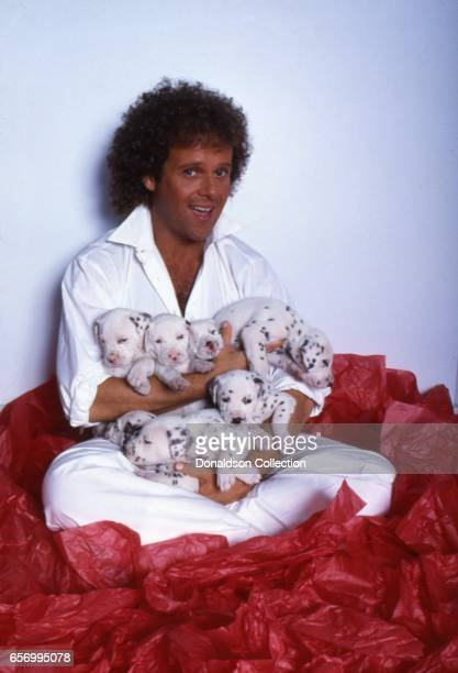 Richard Simmons poses for a portrait with dalmation puppies on July 2 1985 in Los Angeles California