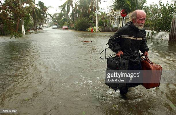 Richard Sorel of Key West Florida carries some of his belongings through flood water along Florida Street caused by Hurricane Wilma as he walks...