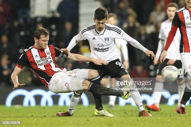 Richard Stearman of Sheffield United kicks the ball out of play in front of Rui Fonte of Fulham during the Sky Bet Championship match between Fulham...