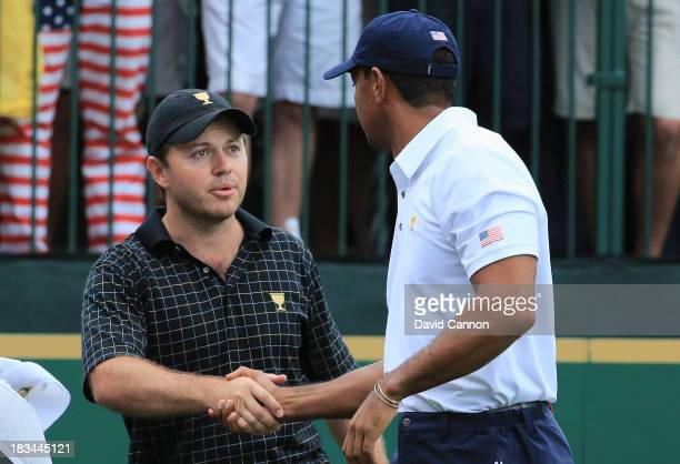Richard Sterne of South Africa and the International Team shakes hands with Tiger Woods of the U.S. Team on the first tee during the Day Four Singles...