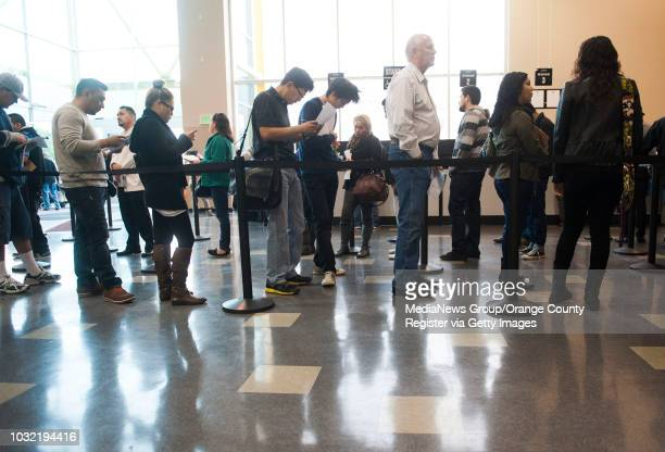 Richard Taylor of Huntington Beach third from right patiently waits in line to get his driver's license renewed at the crowded new DMV office in...