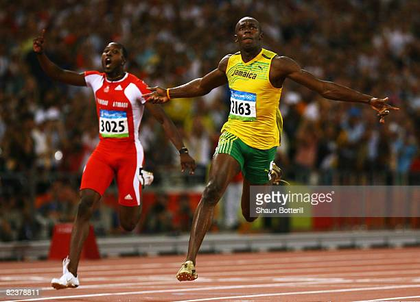 Richard Thompson of Trinidad and Tobago and Usain Bolt of Jamaica cross the line in the Men's 100m Final at the National Stadium on Day 8 of the...