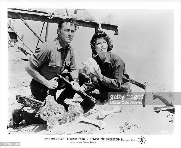 Richard Todd and Marianne Koch with a skull in a scene from the film 'Coast of Skeletons', 1964.