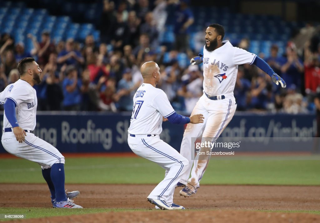 Richard Urena #7 of the Toronto Blue Jays is congratulated by Ryan Goins #17 after hitting the game-winning RBI single in the ninth inning during MLB game action against the Baltimore Orioles at Rogers Centre on September 12, 2017 in Toronto, Canada.