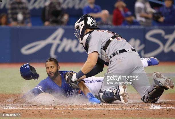Richard Urena of the Toronto Blue Jays is tagged out at home plate by Grayson Greiner of the Detroit Tigers in the tenth inning during MLB game...