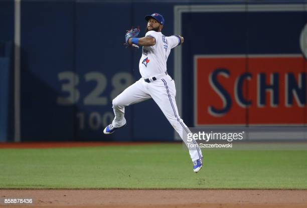 Richard Urena of the Toronto Blue Jays makes a leaping throw in the third inning during MLB game action but cannot throw out Mikie Mahtook of the...