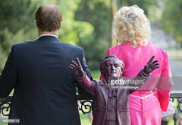 Richard Wagner statue is displayed between visitors at Bayreuth Festival Theatre on August 12, 2014 in Bayreuth, Germany.