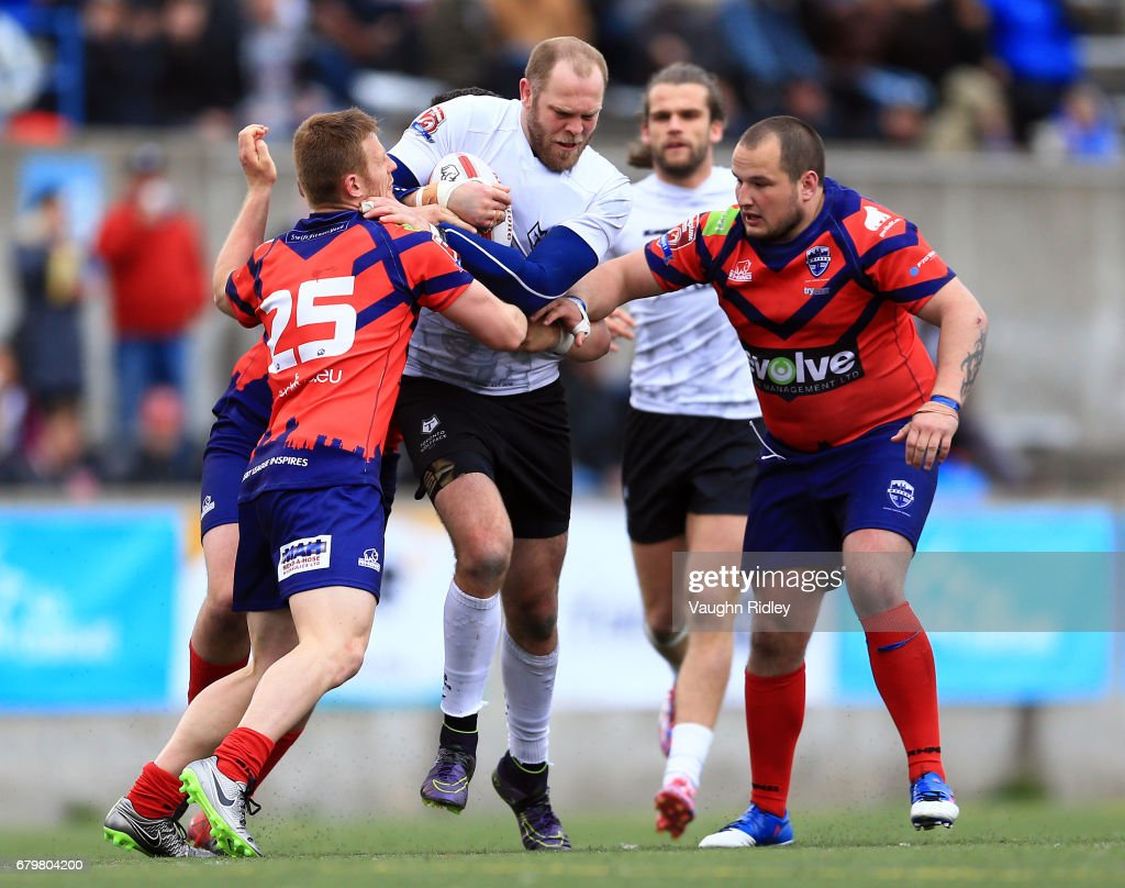 Richard Whiting #17 of Toronto Wolfpack is tackled by Brad Moules #25 and Josh Scott #8 of Oxford RLFC during the second half of a Kingstone Press League 1 match at Lamport Stadium on May 6, 2017 in Toronto, Canada.