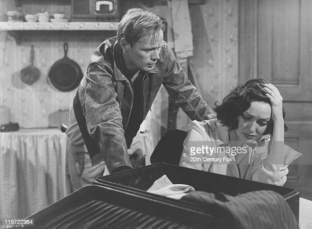 Richard Widmark 1914–2008 US actor leaning over US actress Linda Darnell in a publicity still issued for the film 'No Way Out' USA circa 1950 The...