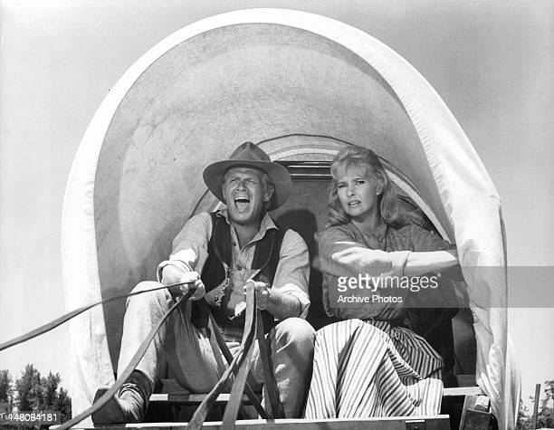 Richard Widmark directs the horses that are pulling he and Lola Albright in a covered wagon in a scene from the film 'The Way West' 1967