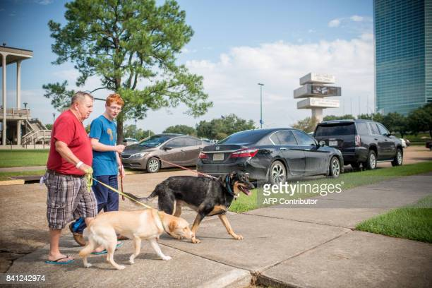 Richard Woodcroft and his son J Woodcroft of Orange Texas walk two of their four dogs near the Lake Charles Civic Center in Lake Charles Louisiana on...