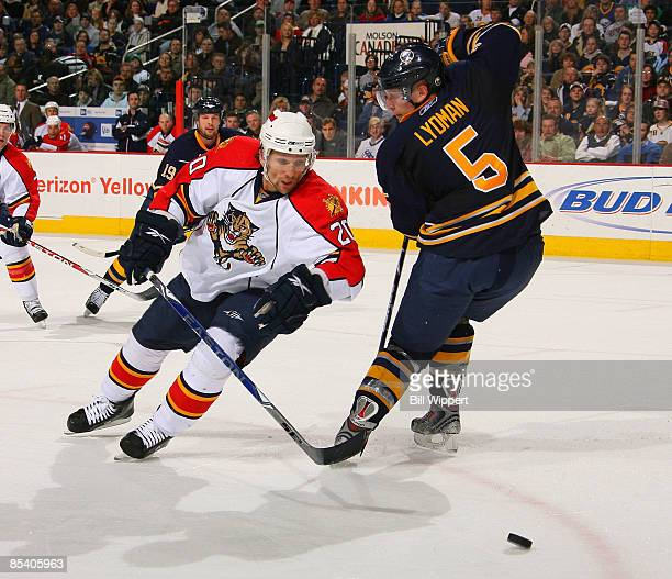 Richard Zednik of the Florida Panthers reaches for the puck as he skates past Toni Lydman of the Buffalo Sabres on March 12, 2009 at HSBC Arena in...