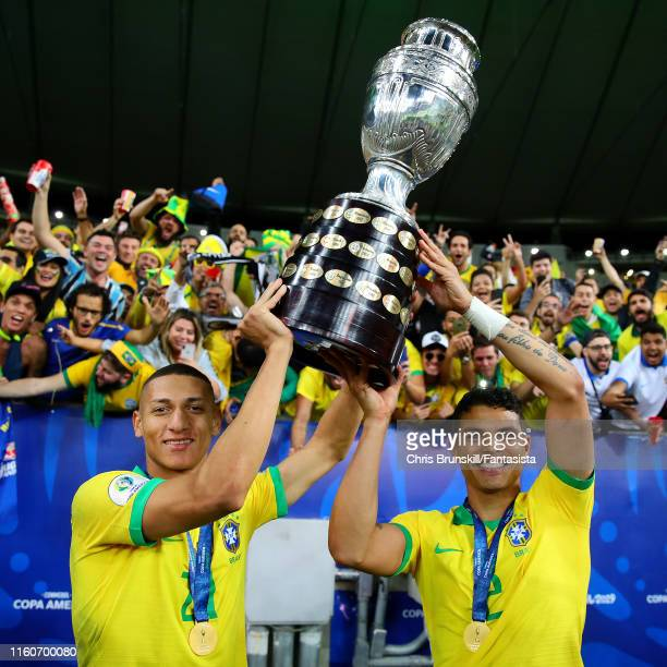 Richarlison and Thiago SIlva of Brazil celebrate with the trophy following the Copa America Brazil 2019 Final match between Brazil and Peru at...