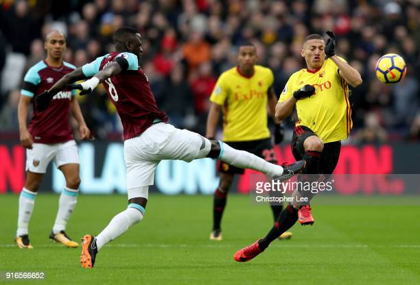 Richarlison de Andrade of Watford is challenged by Cheikhou Kouyate of West Ham United during the Premier League match between West Ham United and...