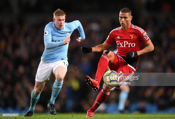 Richarlison de Andrade of Watford is challenged by Kevin De Bruyne of Manchester City during the Premier League match between Manchester City and...