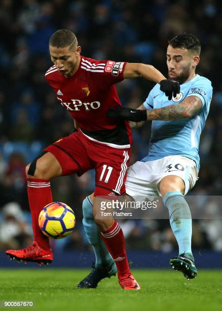 Richarlison de Andrade of Watford is challenged by Nicolas Otamendi of Manchester City during the Premier League match between Manchester City and...