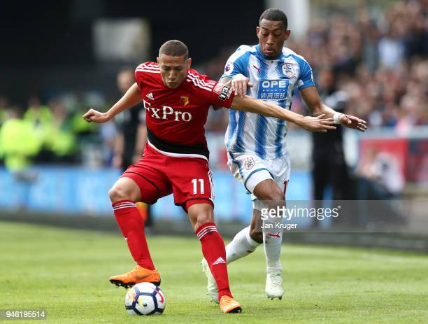 Richarlison de Andrade of Watford is challenged by Rajiv van La Parra of Huddersfield Town during the Premier League match between Huddersfield Town...