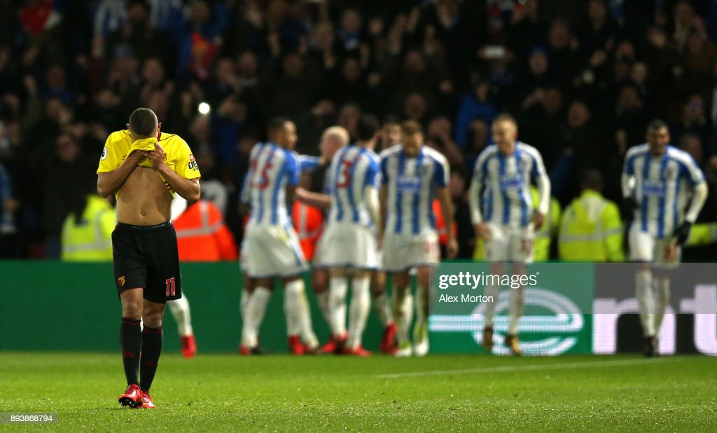 Richarlison de Andrade of Watford look dejected as Huddersfield Town celebrates there fourth goal during the Premier League match between Watford and Huddersfield Town at Vicarage Road on December 16, 2017 in Watford, England.