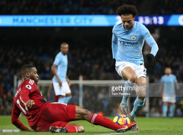 Richarlison de Andrade of Watford tackles Leroy Sane of Manchester City during the Premier League match between Manchester City and Watford at Etihad...