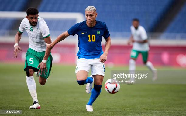 Richarlison of Brazil and Abdulelah Alamri of Saudi Arabia battle for the ball during the Men's Group D match between Saudi Arabia and Brazil on day...