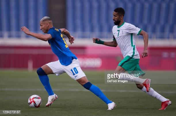 Richarlison of Brazil and Salman Alfaraj of Saudi Arabia battle for the ball during the Men's Group D match between Saudi Arabia and Brazil on day...