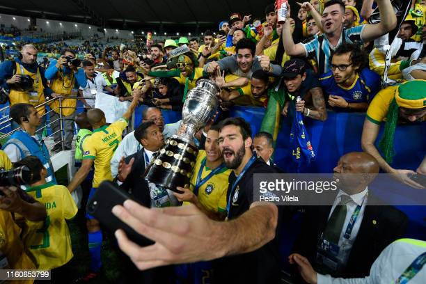 Richarlison of Brazil celebrates with teammate Alisson Becker and the trophy after winning the Copa America Brazil 2019 Final match between Brazil...