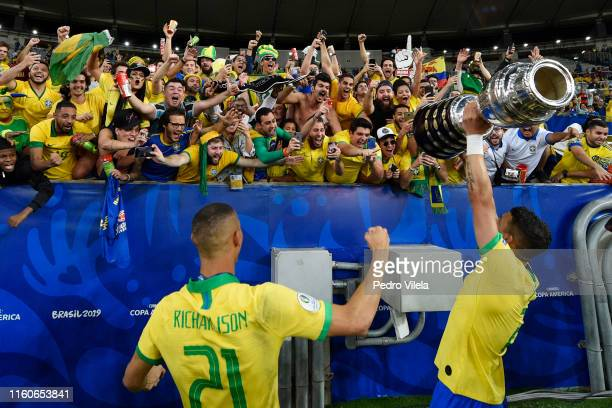 Richarlison of Brazil celebrates with teammate Thiago Silva and the trophy after winning the Copa America Brazil 2019 Final match between Brazil and...