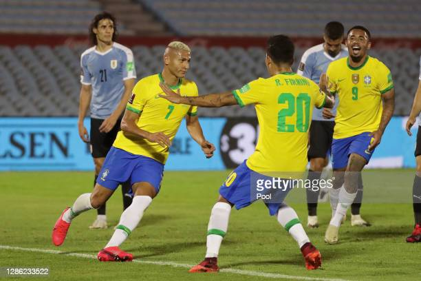 Richarlison of Brazil celebrates with teammates after scoring the second goal of their team during a match between Uruguay and Brazil as part of...