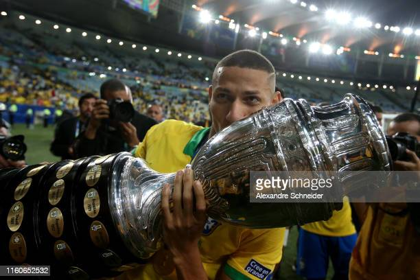 Richarlison of Brazil celebrates with the trophy after winning during the Copa America Brazil 2019 Final match between Brazil and Peru at Maracana...