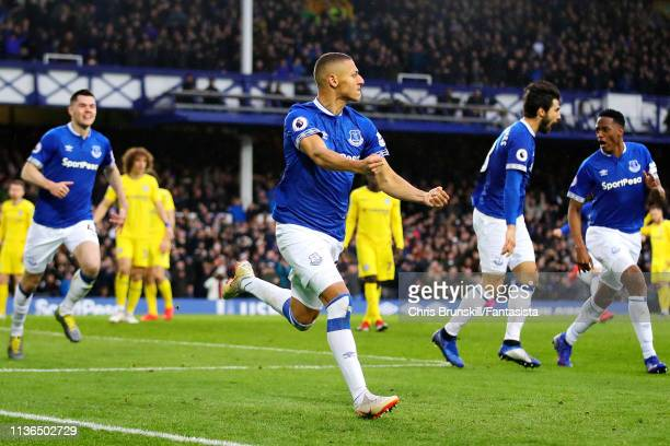 Richarlison of Everton celebrates scoring his sides first goal during the Premier League match between Everton FC and Chelsea FC at Goodison Park on...