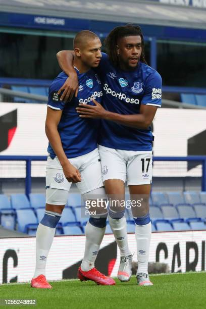 Richarlison of Everton celebrates with Alex Iwobi after scoring his team's first goal during the Premier League match between Everton FC and...