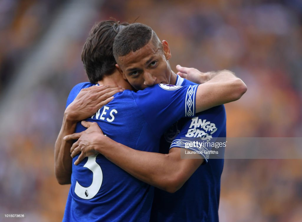 Richarlison of Everton celebrates with teammate Leighton Baines after scoring his team's first goal during the Premier League match between Wolverhampton Wanderers and Everton FC at Molineux on August 11, 2018 in Wolverhampton, United Kingdom.