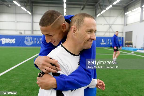 Richarlison of Everton embraces a participant during an Everton in the Community event at USM Finch Farm on September 18 2018 in Halewood England