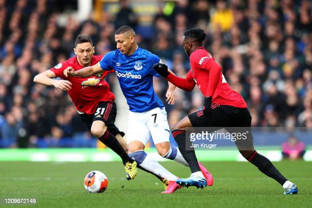 Richarlison of Everton is challenged by Nemanja Matic and Fred of Manchester United during the Premier League match between Everton FC and Manchester...