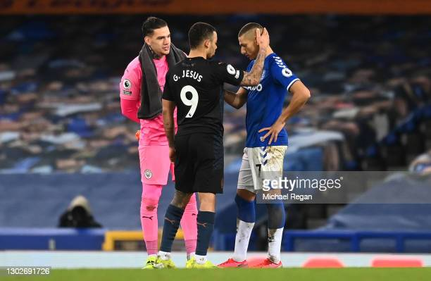 Richarlison of Everton is consoled by Ederson and Gabriel Jesus of Manchester City during the Premier League match between Everton and Manchester...
