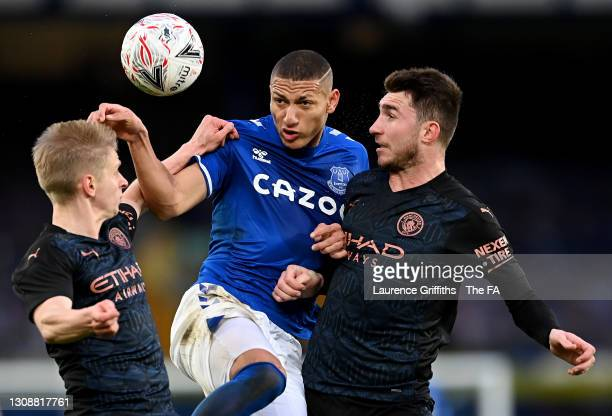 Richarlison of Everton jumps to head the ball under pressure from Oleksandr Zinchenko and Aymeric Laporte of Manchester City during the Emirates FA...