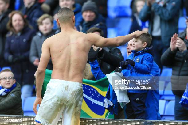 Richarlison of Everton pats a young fan on the head after giving him his shirt following the Premier League match between Everton FC and Crystal...