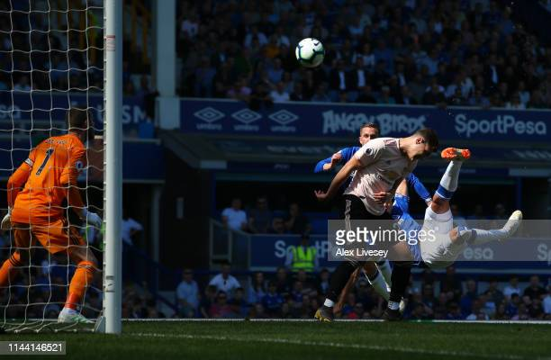 Richarlison of Everton scores his team's first goal past David De Gea of Manchester United as Diogo Dalot of Manchester United challenges during the...