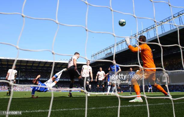 Richarlison of Everton scores his team's first goal past David De Gea of Manchester United during the Premier League match between Everton FC and...