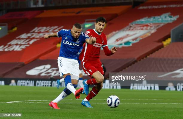 Richarlison of Everton scores his team's first goal whilst under pressure from Ozan Kabak of Liverpool during the Premier League match between...