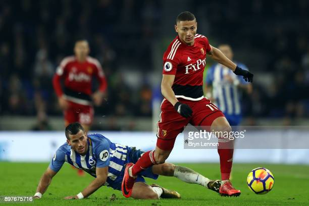 Richarlison of Watford avoids Tomer Hemed of Brighton Hove Albion during the Premier League match between Brighton and Hove Albion and Watford at...