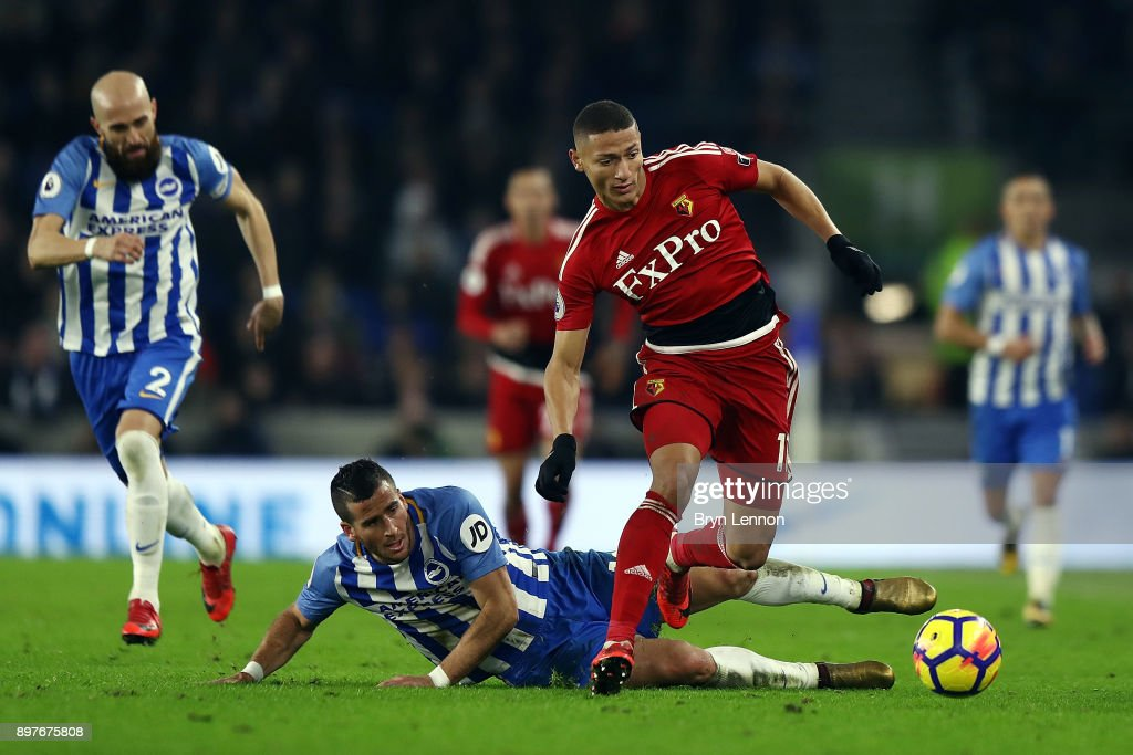Richarlison of Watford avoids Tomer Hemed of Brighton & Hove Albion during the Premier League match between Brighton and Hove Albion and Watford at Amex Stadium on December 23, 2017 in Brighton, England.