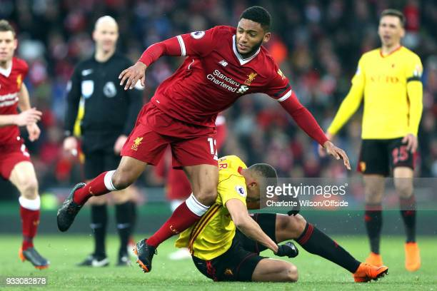 Richarlison of Watford goes to ground after battling with Joe Gomez of Liverpool during the Premier League match between Liverpool and Watford at...