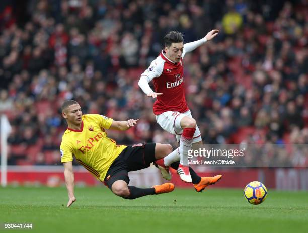 Richarlison of Watford tackles Mesut Ozil of Arsenal during the Premier League match between Arsenal and Watford at Emirates Stadium on March 11 2018...