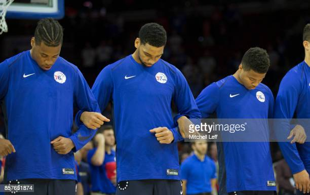 Richaun Holmes Jahlil Okafor and Markelle Fultz of the Philadelphia 76ers lock arms during the national anthem prior to the preseason game against...