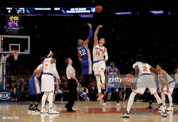 Richaun Holmes of the Philadelphia 76ers and Willy Hernangomez of the New York Knicks go up for the opening tipoff at Madison Square Garden on April...