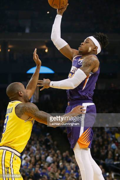 Richaun Holmes of the Phoenix Suns shoots the ball over Andre Iguodala of the Golden State Warriors at ORACLE Arena on March 10 2019 in Oakland...