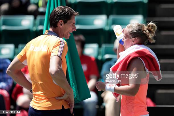 Richel Hogenkamp of the Netherlands drinks from a bottle while team captain Paul Haarhuis of the Netherlands talks to her in her singles match...
