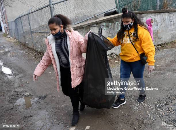 Richeldys Herhadez and Jennifer Lopez carry the trash bag as they and other club members pick up trash around the club. At the Olivet Boys and Girls...